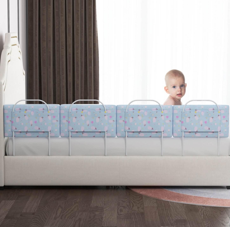 copil care sta in pat cu mini-bumpere monatte pe o latura