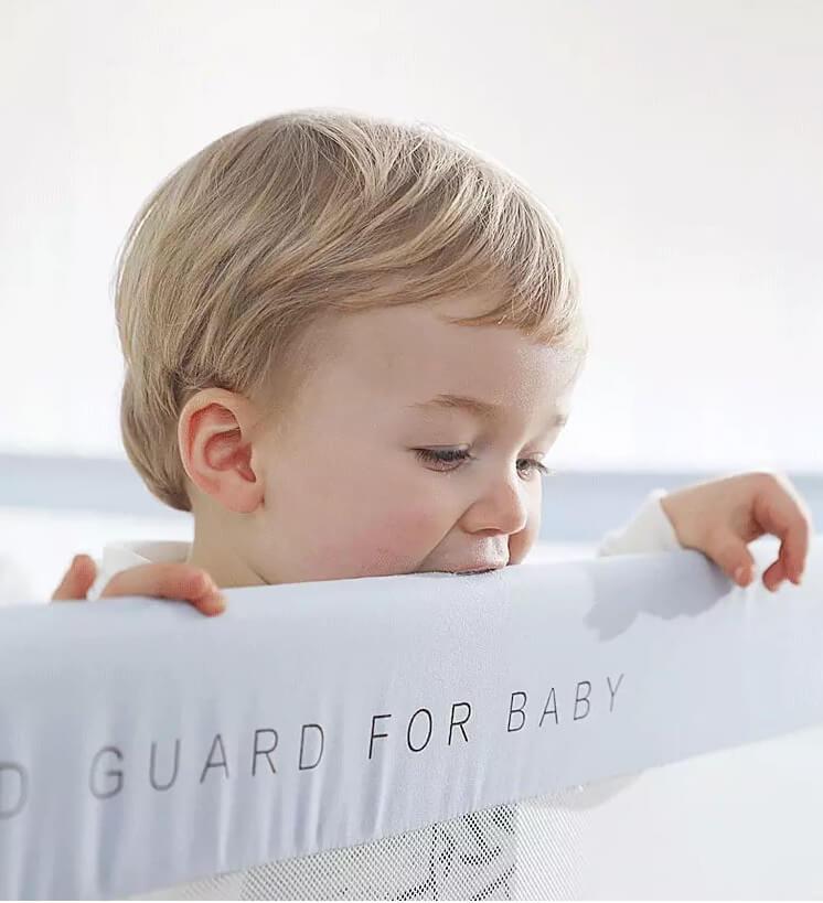 Copil care musca dintr-o bariera de pat