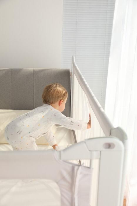 Bariera de pat si copil care apasa pe plasa