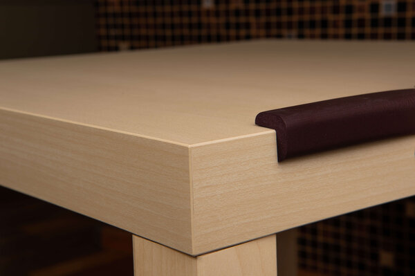 Banda groasa de protectie pentru mobilier montata pe o masa de lemn, asigurand protectia copiilor impotriva loviturilor
