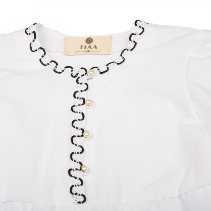 Bluză din poplin (bumbac 100%) cu mâneci 3/4, ce au la bază un volan amplu. Închiderea se face în față cu nasturi. Pe mâneci și la baza gâtului are aplicată o bandă decorativă în alb și negru.  POPLINUL este o țesătură de bumbac mercerizat, cu fire de urzeală subțiri, netedă și foarte fină folosită pentru confecționarea cămășilor. 2