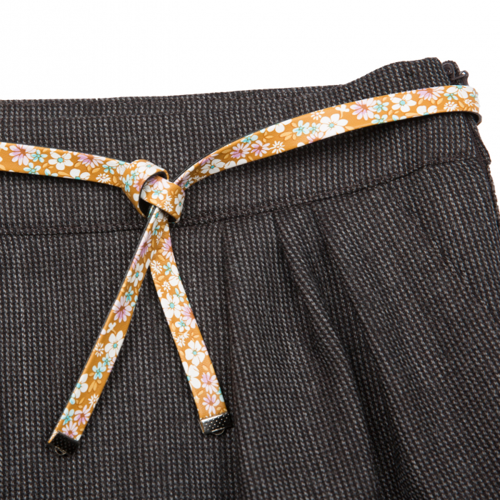 Fustă de lână (80%) creată dintr-un material moale, foarte plăcut la purtat. Aceasta are un design modern cu buzunare laterale, tiv intors și curelușă înflorată.  Încălțată cu o pereche de bocanci, ghetuțe sau chiar cizme, fetița dumneavoastră va stârni admirația prietenelor. 2