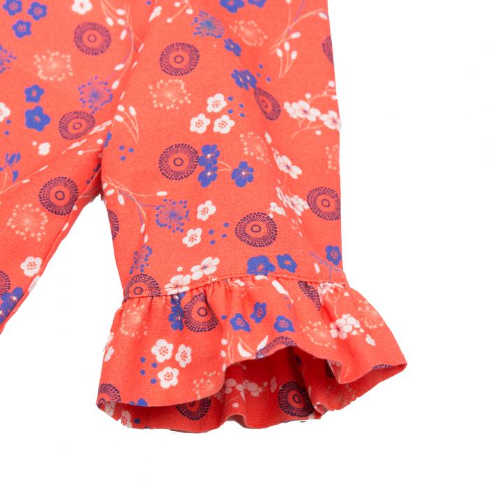 Rochiță elegantă din percal (bumbac 100%), având un design cu flori colorate și mandala pe fundal roșu. Mandala este o imagine-simbol, reprezentată printr-un cerc magic, simbolizând universul și armonia. Rochița are volane la mâneci si la tiv. Cordonul cu fundă este atașat. Închiderea se face în spate, până în talie, cu fermoar ascuns, pentru a nu crea disconfort. 3
