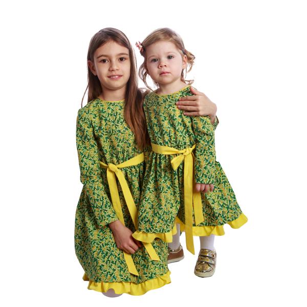 Rochiță veselă creată dintr-un material moale, foarte plăcut la purtat. Desenul reprezintă un puzzle de flori mici in diverse nuante de galben si verde.  Rochița are un volan galben la tiv și se leagă în talie cu un cordon în culoarea acestuia. Închiderea se face în spate, până în talie, cu nasturi mici, plați, pentru a nu crea disconfort. 3