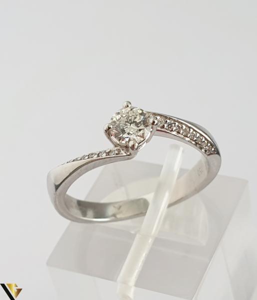 """Inel aur alb 18k, 750 3.42 grame Diamant """"briliant"""" central de cca. 0.33 ct, incadrat de 4 gheare masive, turnate si cizelate Anturaj pe fiecare laterala format din cate 9 diamante circulare de cca. 0.005 ct, aliniate si asigurate individual prin perlare Diametrul inelului este de 17 mm Marcaj cu titlul """"750"""" Locatie HARLAU 30049 0"""