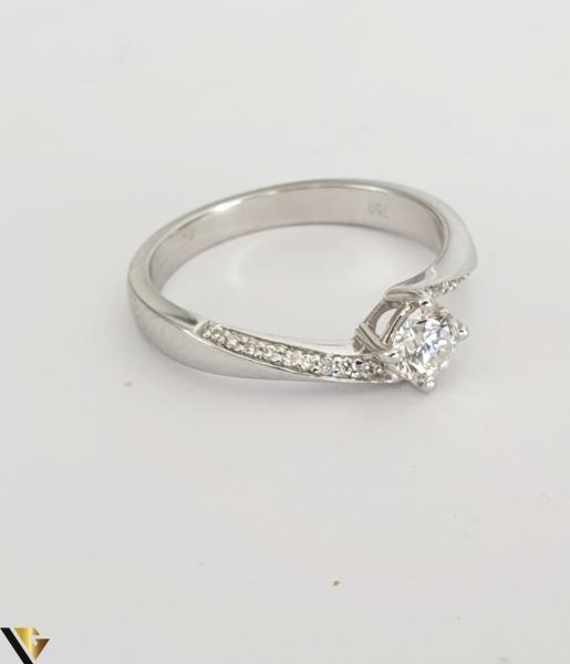 """Inel aur alb 18k, 750 3.42 grame Diamant """"briliant"""" central de cca. 0.33 ct, incadrat de 4 gheare masive, turnate si cizelate Anturaj pe fiecare laterala format din cate 9 diamante circulare de cca. 0.005 ct, aliniate si asigurate individual prin perlare Diametrul inelului este de 17 mm Marcaj cu titlul """"750"""" Locatie HARLAU 30049 2"""