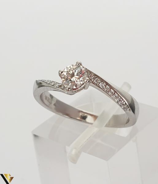 """Inel aur alb 18k, 750 3.42 grame Diamant """"briliant"""" central de cca. 0.33 ct, incadrat de 4 gheare masive, turnate si cizelate Anturaj pe fiecare laterala format din cate 9 diamante circulare de cca. 0.005 ct, aliniate si asigurate individual prin perlare Diametrul inelului este de 17 mm Marcaj cu titlul """"750"""" Locatie HARLAU 30049 1"""