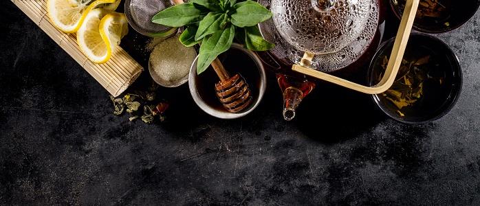 Beautiful Tea Ceremony Glass Teapot Honey Mint Lemon Cups on Dark Table Background Closeup Horizontal